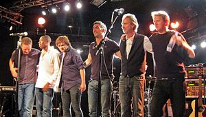 Mike + The Mechanics in 2012 L-R: Ben Stone, Andrew Roachford, Tim Howar, Luke Juby, Mike Rutherford and Anthony Drennan