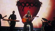 Image of a blonde woman sitting on a stool. She's wearing a black sleeveless shirt and black pants. She is holding an orange acoustic guitar in her hands. A microphone stands before her. Other instruments and musicians can be seen in the background.
