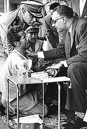 A man on his knees looking up to a man sitting and holding his hand and wearing sun glasses, has his right hand on his shoulder and is talking to him. In the background there are men in military uniform all looking on the kneeling man.
