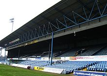 "An imposing colour shot of a traditional British-style grandstand, mostly painted blue and filled with blue seats. A sign around its centre, hanging from the ceiling, reads ""Cardiff City F.C.""."