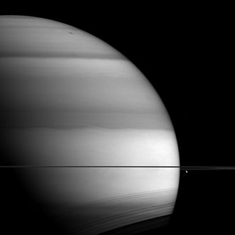 Saturn - Methane bands circle Saturn. The moon Dione hangs below the rings to the right.