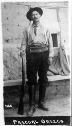 A black-and-white photograph of a man in a cowboy hat, a cartridge belt around his waist and a rifle by his foot, looking straight at the camera