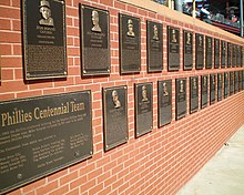 A double row of two-tone bronze-colored plaques mounted on a brick wall