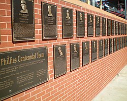 "A succession of black metal plaques mounted on a brick wall. In the foreground is one plaque larger than the other entitled ""Phillies Centennial Team"". The smaller plaques each have a face and inscribed text."