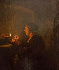 A woman sewing near an oil lamp