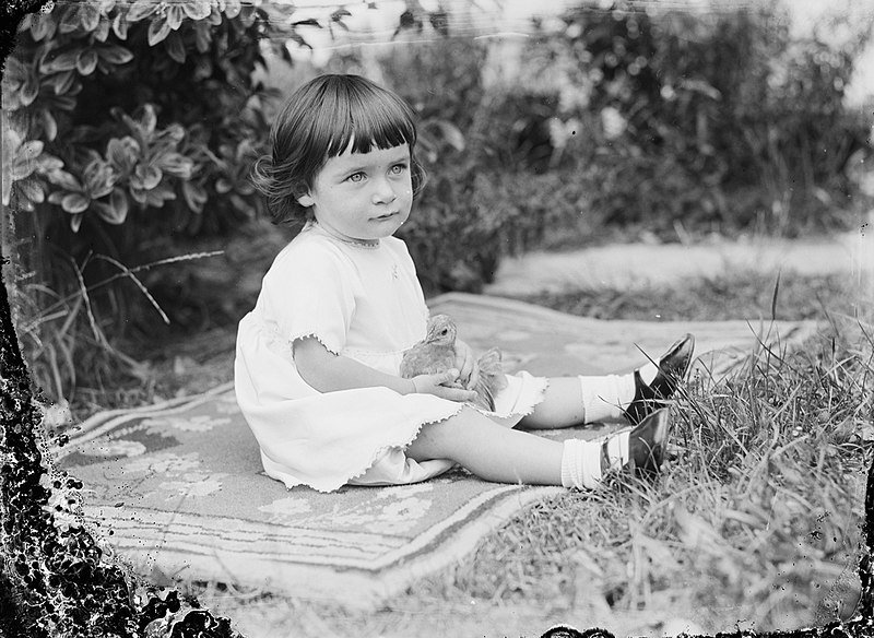 File:Portrait of a toddler girl seated on a patterned rug on the grass (AM 76336-1).jpg