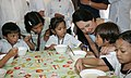 """President Gloria Macapagal-Arroyo enjoins one of the malnourished children to eat """"sopas"""" during a feeding program acitivity 02.jpg"""