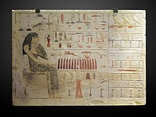A flat limestone block with a painted, carved raised-relief of woman in spotted linen cloth, seated near table with food items. Painted hieroglyphs decorate the rest of the surface.
