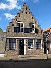 foto van Huis met trapgevel. Sierankers. Na de oorlog geheel vernieuwd. Boven: houten kruisramen. Beneden: puibalk, ramen 18e-eeuws