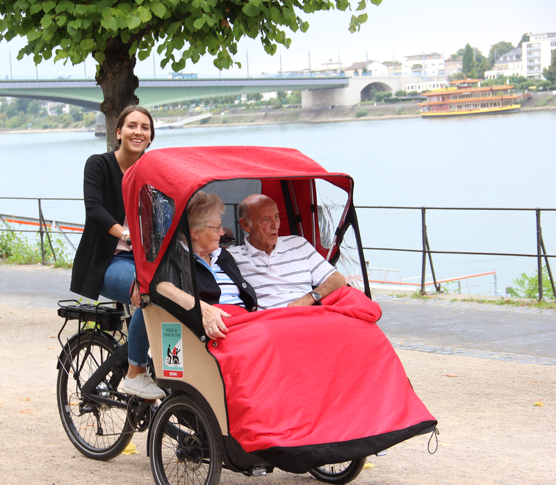 A young lady drives a trishaw with two elderly persons along the Rhine river near Bonn, Germany