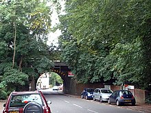A street with several parked cars and large trees is crossed by a railway bridge