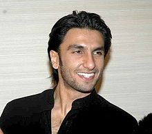 Singh looking towards his left and smiling, wearing a black T-shirt