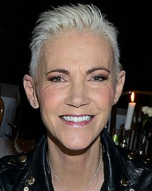 An image of a short-haired woman smiling in to a camera. There is a flame from a candle flickering above her left shoulder.