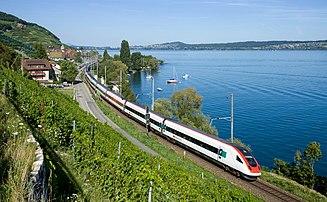 Duas unidades de material rolante SBB RABDe 500 circulam pela ferrovia Jurafusslinie, às margens do Lago de Bienna, em Twann, cantão de Berna, Suíça.  (definição 4324×2669)