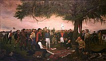 A group of men are gathered under a large tree.  One man lays on the ground under the trees, with his bare foot exposed.