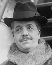 plumpish middle-aged man with neat moustache, wearing a hat