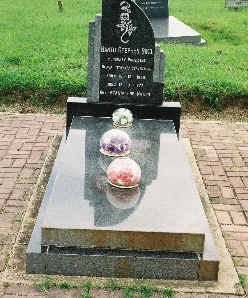A grave and headstone. The structure is made from a shiny grey rock, and lacks ornamentation. Three flowers encased in circular glass baubles sit on top of it.