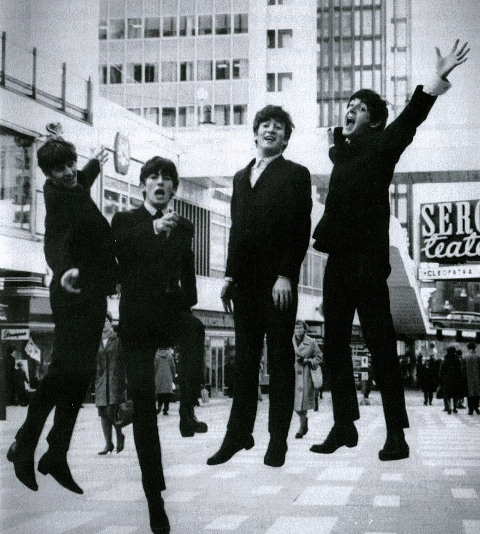 A black and white image of four suited men captured mid-jump