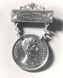 "The engraving on the top bar reads ""THOMAS PETERSON, Perth Amboy"". The hanging medallion is attached to the top bar using two chains. The hanging medallion shows a profile bust of a clean-shaven Abraham Lincoln."