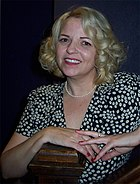 A woman with blond hair, wearing a black and white outfit.
