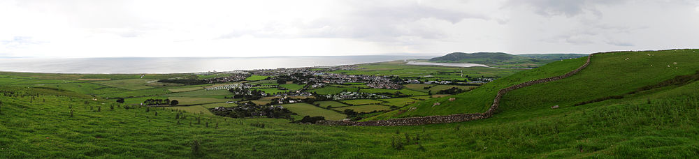 Panorama of the Welsh town Tywyn showing it nestled between hills and with the sea behind. A reservoir is visible in the background.