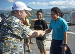 U.S. Ambassador to Samoa David Huebner, left, shakes a Samoan student athlete's hand and gives her a command coin as he gives the students a tour of the flight deck of the amphibious dock landing ship USS Pearl 130604-N-WD757-127.jpg