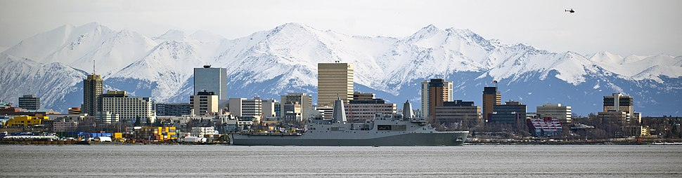 The USS Anchorage departing from its eponymous port in May 2013. The vessel is framed by the city's downtown and the Chugach Mountain Range in the background.
