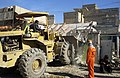 US Navy 041213-N-4614W-027 A front-end loader picks up the remains of a stonewall as Iraqi contractors clear approximately three blocks of broken walls, glass, and trash from a major thoroughfare in Fallujah, Iraq.jpg