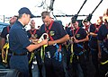 US Navy 050823-N-9076B-002 Electronics Technician 2nd Class Edwin Dillaby, left, helps a chief selectee with a safety harness during an up and over drill were the selectees climb the mast and come down the other side aboard USS.jpg