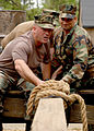 US Navy 070426-N-0553R-005 Senior Chief Equipment Operator Mark Thomas and Chief Construction Mechanic Ronaldo Rodriguez, assigned to Naval Mobile Construction Battalion (NMCB) 1, use teamwork to maneuver a wooden plank.jpg