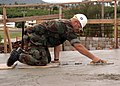 US Navy 070912-F-8678B-105 Chief Utilitiesman James A. Deneen, attached to Naval Mobile Construction Battalion (NMCB) 4, uses a magnesium hand float to finish concrete during an overhead concrete pour at Orote Point quarry.jpg