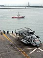 US Navy 071219-N-4774B-024 Sailors standing beside a CH-53E Super Stallion helicopter watch as a tugboat, which had just pushed amphibious assault ship USS Tarawa (LHA 1) out of the port of Singapore.jpg