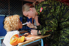 US Navy 080817-N-7955L-035 Canadian Air Force Pvt. Tabitha Beynen, embarked aboard the amphibious assault ship USS Kearsarge (LHD 3), uses a syringe to give de-worming medication into a child.jpg