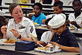 US Navy 090428-N-4124C-003 Operations Specialist Seaman April Guenther, assigned to the guided-missile destroyer USS Forrest Sherman (DDG 98), eats with students at Peters Elementary School during Fleet Week Port Everglades 200.jpg