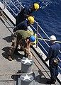 US Navy 100621-N-1082Z-048 Sailors and Marines tie stops on a mooring line aboard the amphibious dock landing ship USS Ashland (LSD 48).jpg