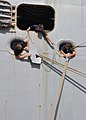 US Navy 100804-N-6566M-015 Sailors aboard USS Iwo Jima (LHD 7) apply rat guards during mooring operations as the ship ports at Naval Station Guantanamo Bay, Cuba, for refueling and supplies.jpg