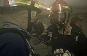US Navy 111220-N-VO377-286 Sailors discuss firefighting strategies prior to fighting a simulated fire during a general quarters drill aboard the Ni.jpg