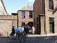 A crowd of visitors enter the former jute factory's courtyard, surrounded by sandstone-built, Georgian-style industrial buildings.