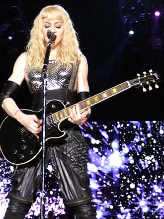 "Ray of Light (song) - Madonna, wearing a futuristic outfit and playing the electric guitar, singing ""Ray of Light"" during the 2008-09 Sticky & Sweet Tour."