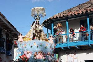 Our Lady of Mount Carmel - A saqra (animal figure) dancer watching the procession of Mamacha Carmen from a balcony