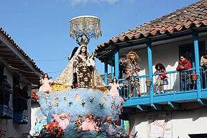 Paucartambo District, Paucartambo - A saqra dancer watching the procession of Mamacha Carmen from a balcony