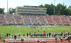 Football stadium with two teams on the field and stands full on sunny day