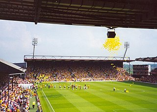 In the background and to the left are two large stands, each of which seem capable of holding thousands of people. In the foreground is a well maintained grass pitch. Yellow balloons can be seen in the sky.