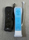 A black Wii Remote Plus in a black jacket next to a blue Wii Remote and white Wii MotionPlus