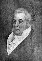 A slightly portly, clean-shaven man with long gray hair wearing a high-collared, white shirt and black jacket