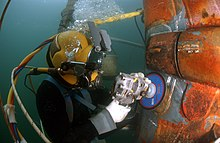 Diver wearing a diving helmet is sanding a repair patch on a submarine