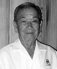 "Head and shoulders of an elderly man wearing a white button shirt with an emblem on the left breast bearing the text ""442"" and ""GO FOR BROKE""."