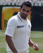 Indian fast-bowler Zaheer Khan walking up to his run-up in the middle of an over. Khan is a dark skinned person, wearing a white shirt. The cricket field can be seen in the background.