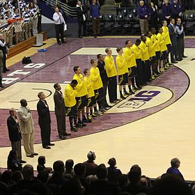 Michigan basketball team in blue uniforms with gold (maize) tops during the national anthem