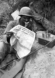 A black soldier rests and reads a newspaper